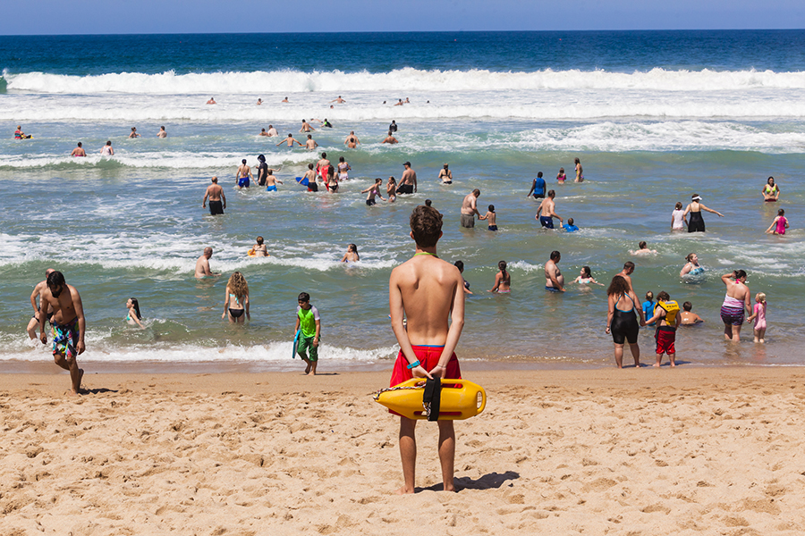 Ramsgate South Coast, South Africa - October 4, 2015: Lifeguard with safety rescue swimming buoy watching public swim in ocean waves