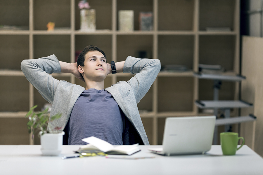 Young Man in casual Jacket sitting at grey working Place with Computer Flower Papers and Tea Mug relaxed Posture smiling thinking pensive Face expression on wooden Wall Background