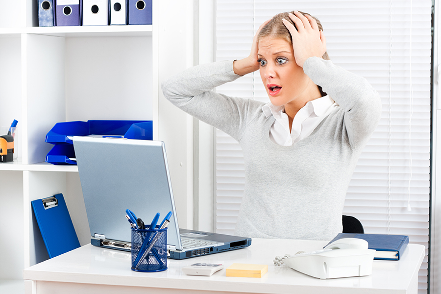 Young businesswoman is shocked by something she sees on her laptop monitor.