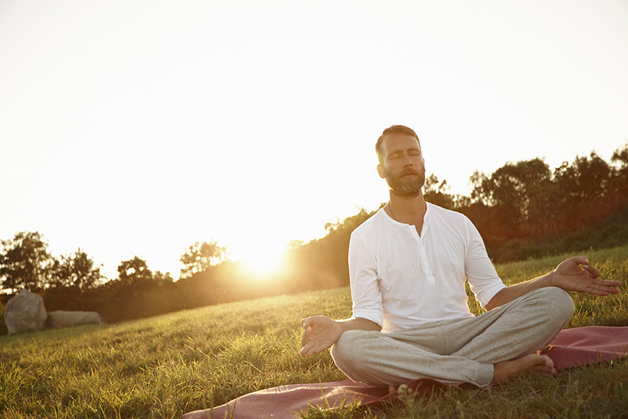 Shot of a handsome mature man meditating in the outdoors at sunset