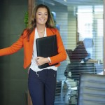 a young graduate walks into an interview room full of confidence and positivity energy . She is holding her cv and smiling at the interview panel before her. She is wearing blue trousers with an orange suit jacket , as she opens the door and strides in.