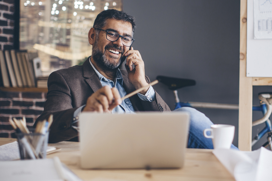 Mature business man working at modern office space, working on project. Making a call on mobile phone at his desk.  Brick wall and bicycle in  background.