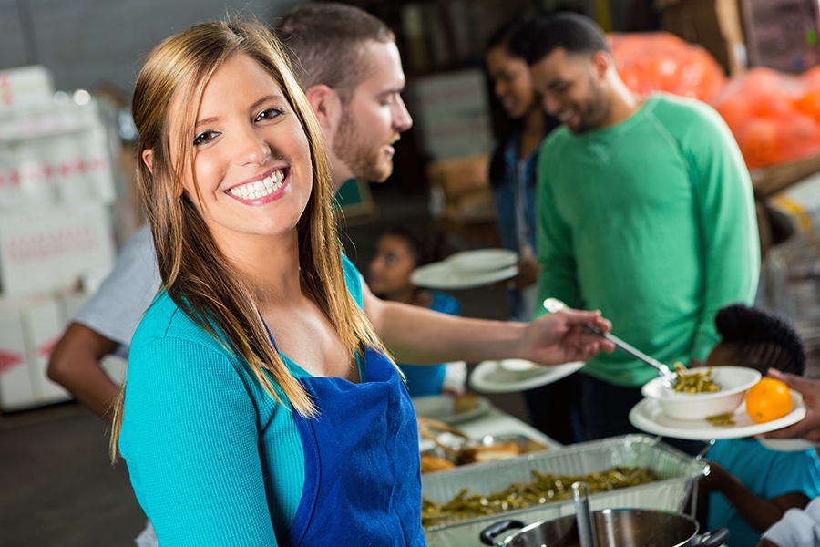 Pretty mid adult woman smiles as she serves meal in local soup kitchen. She is wearing a blue apron. She is holding a serving spoon. Volunteers are serving the people in the line.