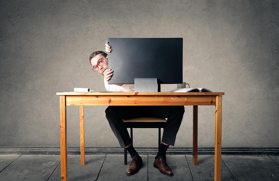 Businessman is hiding behind a computer screen
