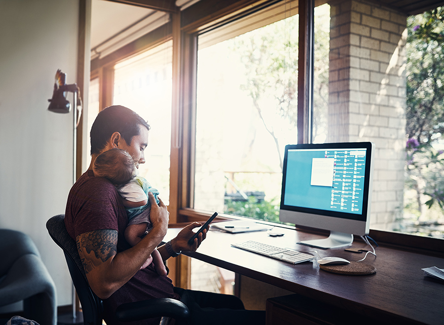 Shot of a young man working at home while holding his newborn baby son