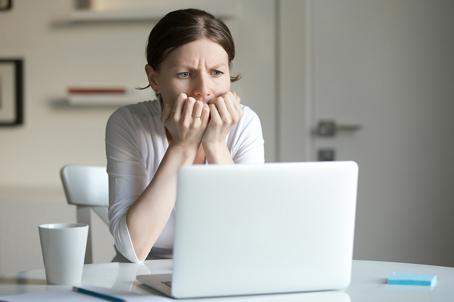 Portrait of a young woman at the desk with a laptop, her hands at her face at a fear. Business concept photo, lifestyle
