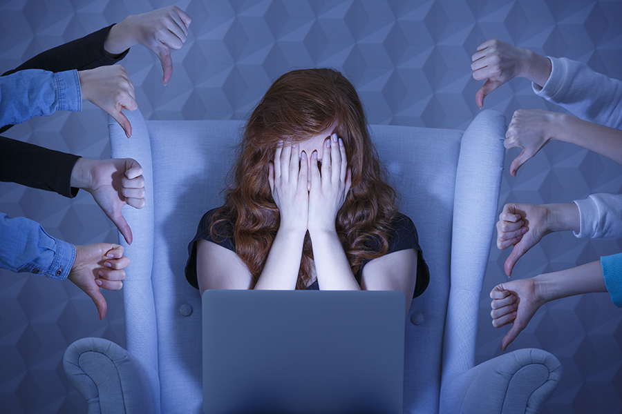 Girl with laptop covering face, around hands holding thumbs down
