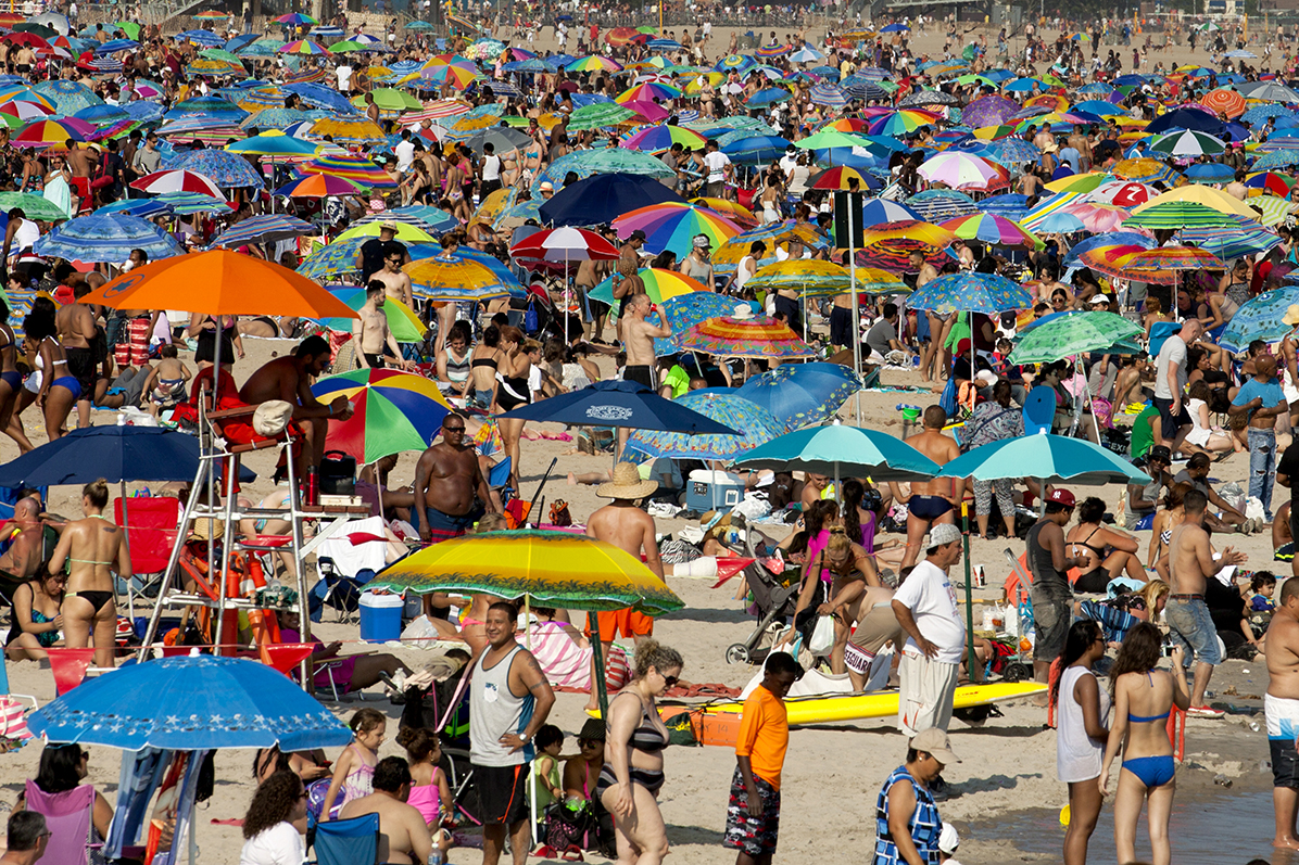 Coney Island, New York, USA - July 11, 2015: Beach crowded with sunbathers and swimmers in Coney Island on a warm summer day in July. Coney Island is a popular summer time vacation destination and local retreat for New Yorkers.